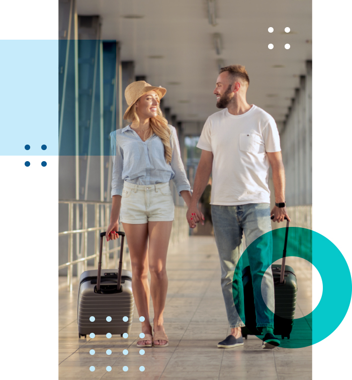 couple holding hands with suitcases